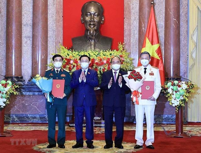 Chủ tịch nước Nguyễn Xuân Phúc trao quyết định, Chủ tịch Quốc hội Vương Đình Huệ tặng hoa cho Bộ trưởng Bộ Công an, Đại tướng Tô Lâm và Bộ trưởng Bộ Quốc phòng, Đại tướng Phan Văn Giang (Ảnh: Thống Nhất/TTXVN).