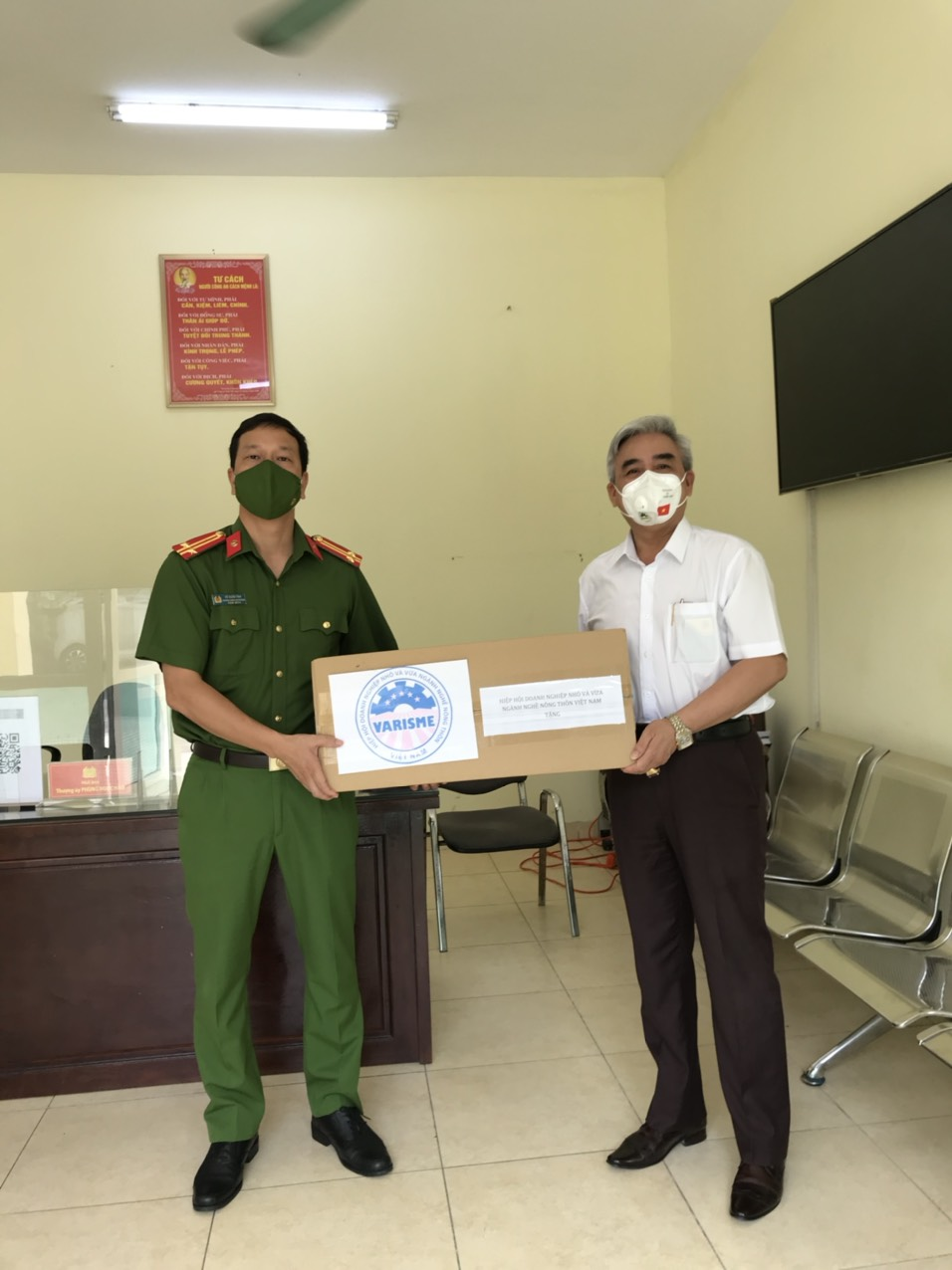 Đại diện công an phường Bồ Đề tiếp nhận khẩu trang y tế N95 từ Chủ tịch Hiệp hội Varisme.