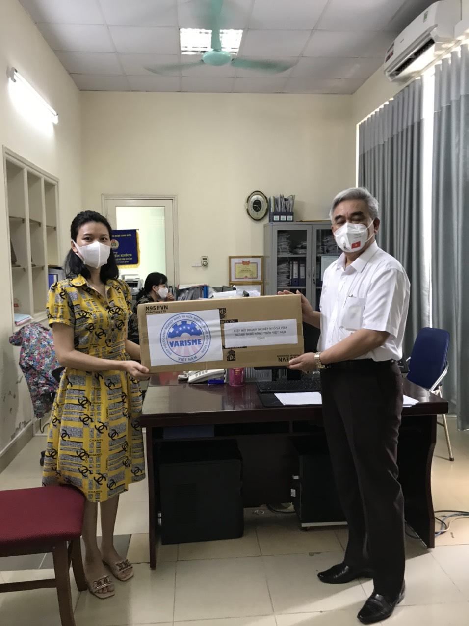 Đại diện UBND phường Long Biên tiếp nhận khẩu trang y tế từ Chủ tịch Hiệp hội Varisme.