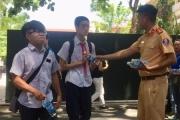 Chiến sĩ cảnh sát giao thông tặng nước mát cho sĩ tử ngay cổng trường thi